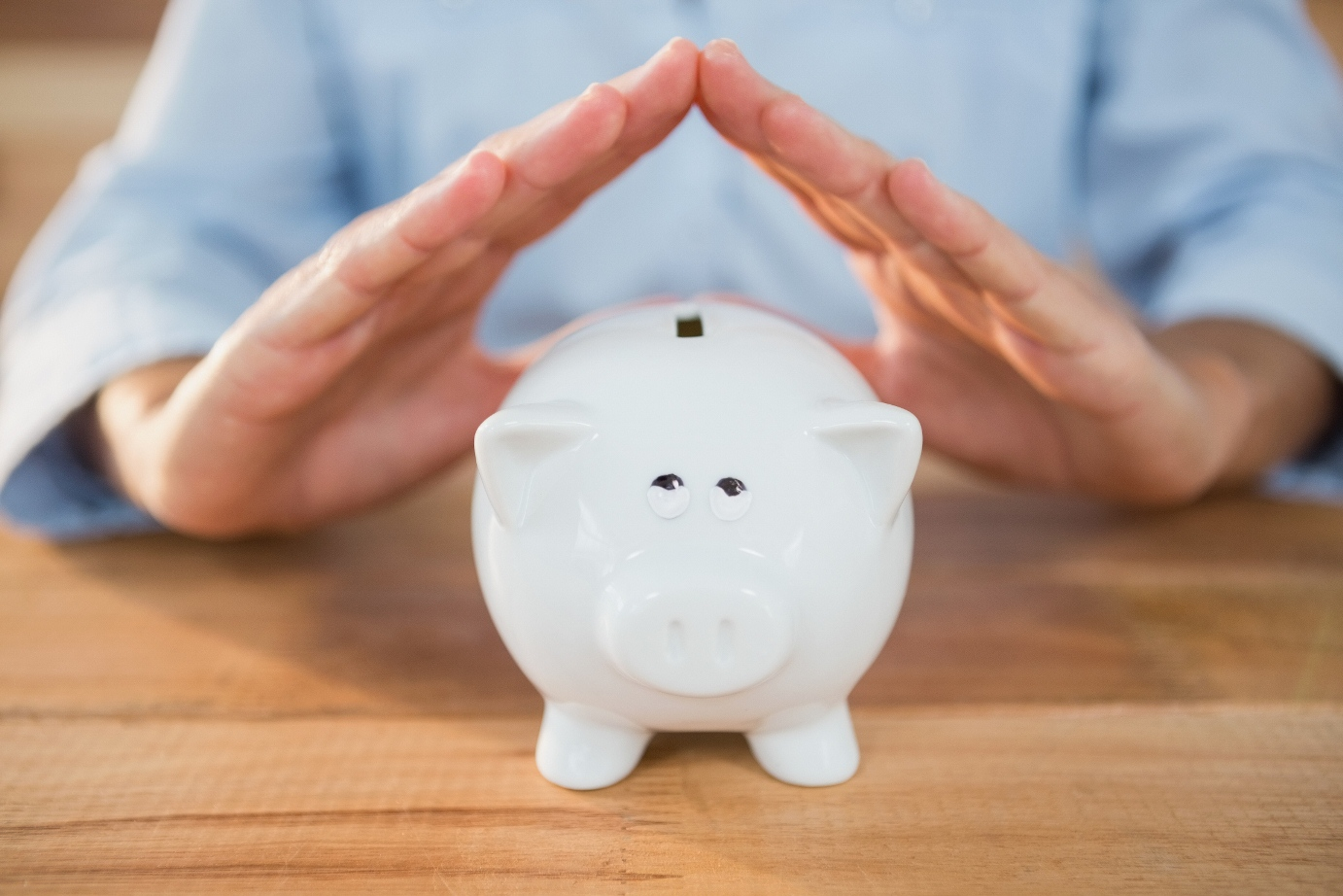 Mid section of man making a roof gesture on piggy bank